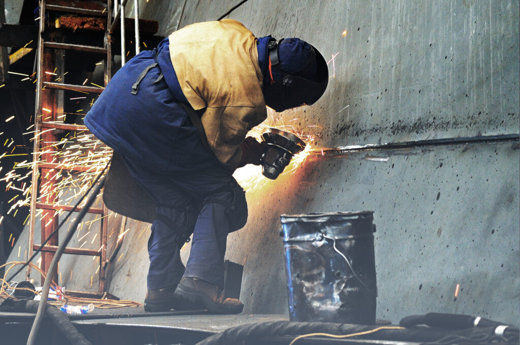 Welder cleaning metal during portable welding service